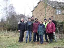 Volunteers standing proud by planted row of cherry trees
